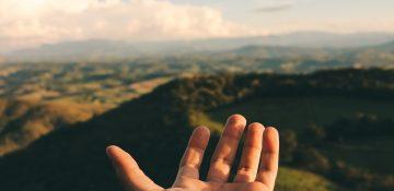 linke hand vor landschaft